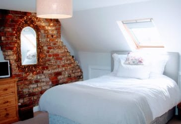 Bright and airy loft conversion bedroom with exposed brick wall and velux window